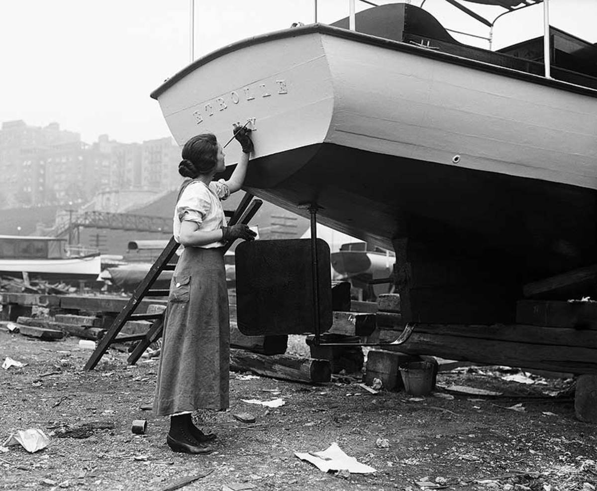 A woman letters a boat's name on the transom in this 1916 photo.