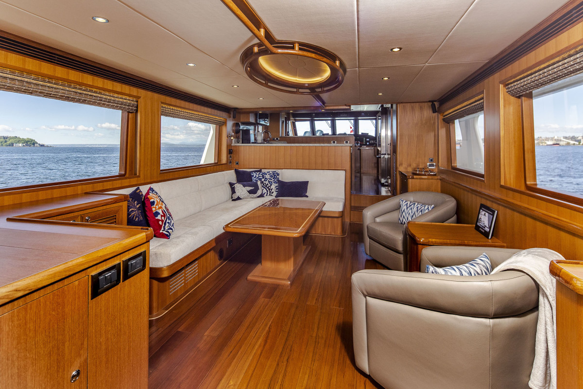 The open concept layout allows sightlines that stretch from the aft deck all the way forward to the pilothouse (note the custom overhead wood handrail with recessed lights)