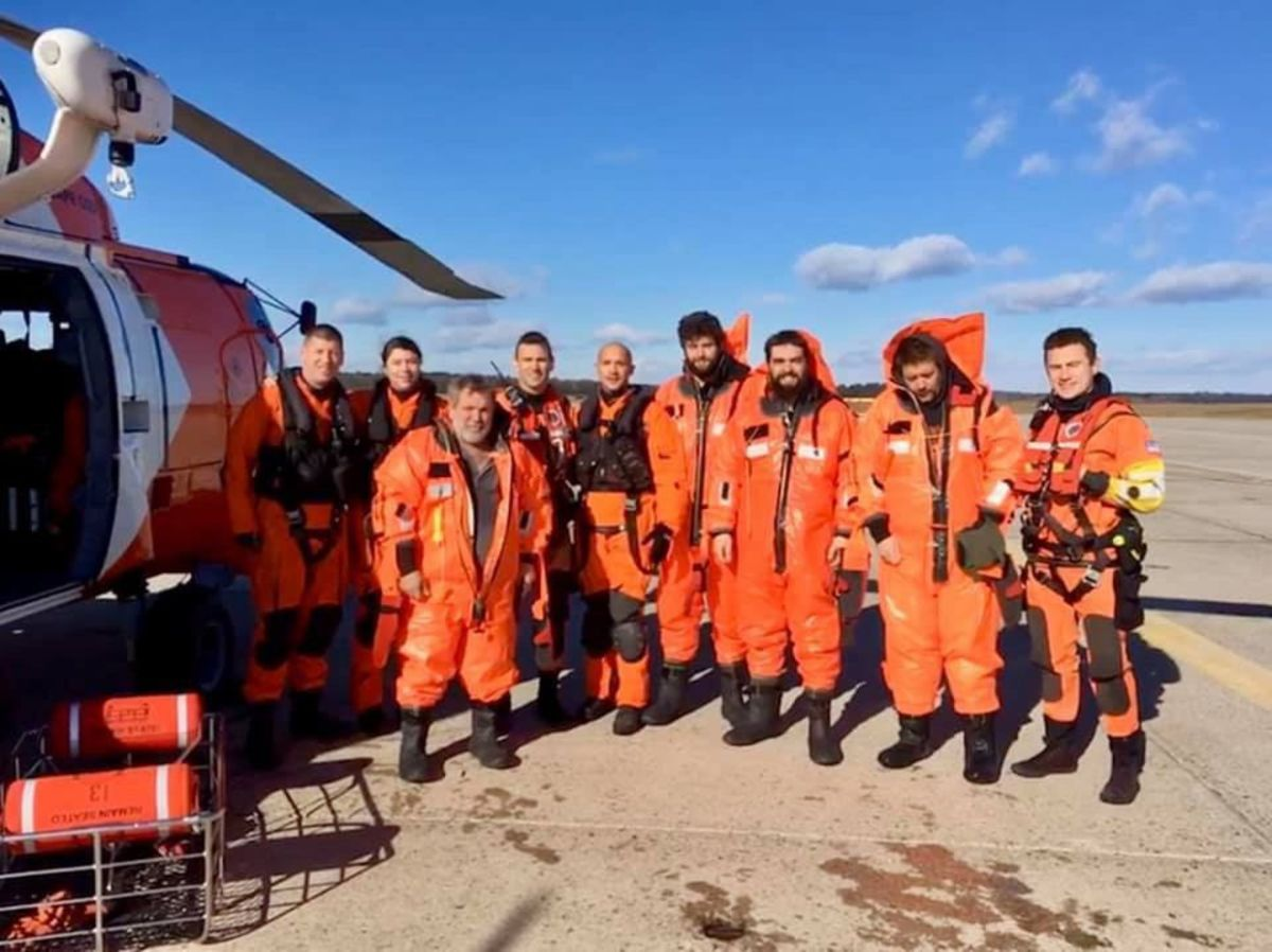 The Air Station Cape Cod rescue aircrews and the rescued four fishermen from the fishing boat Aaron & Melissa II pose for a group photograph at Brunswick Executive Airport in Brunswick, Maine, Wednesday, Nov. 14, 2018.