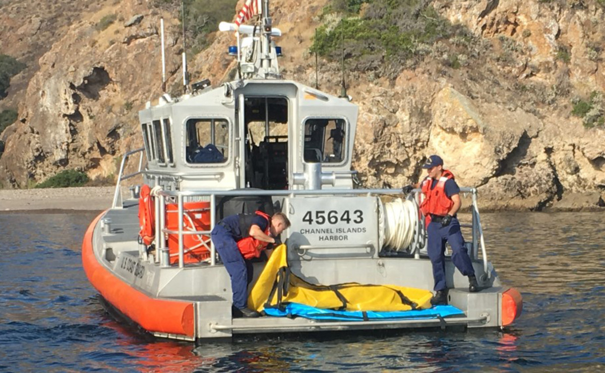 The Coast Guard loading a body bag.