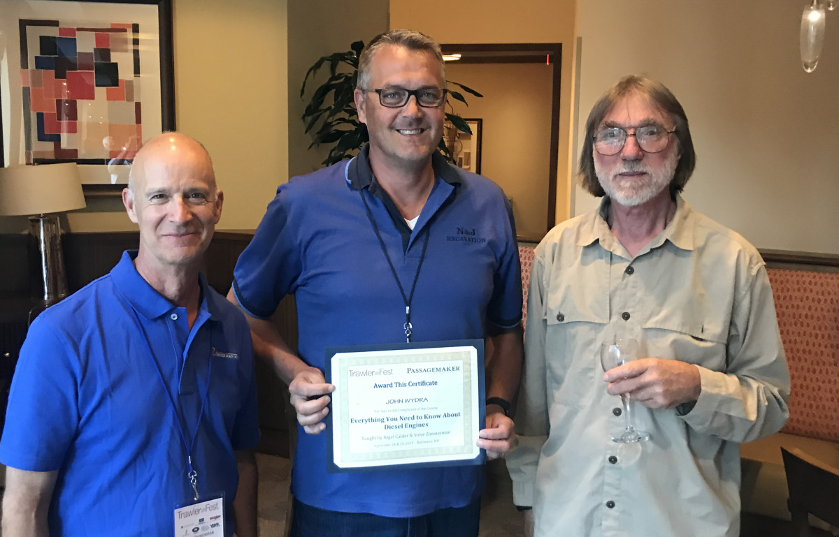 John Wydra receives his Diesel certificate from Steve Zimmerman (left) and Nigel Calder.