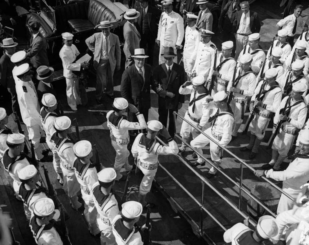 The crew of the Sequoia presents arms as President Franklin D. Roosevelt, supported by his son James Roosevelt, boards the vessel at New Haven in June 1934 en route to New London for the Harvard-Yale Regatta.