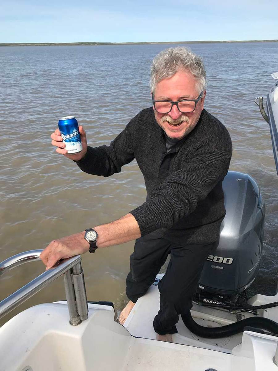 The author enjoys the sweet taste of success while celebrating the end of an adventure with a well-earned toe dip in the Arctic Ocean.