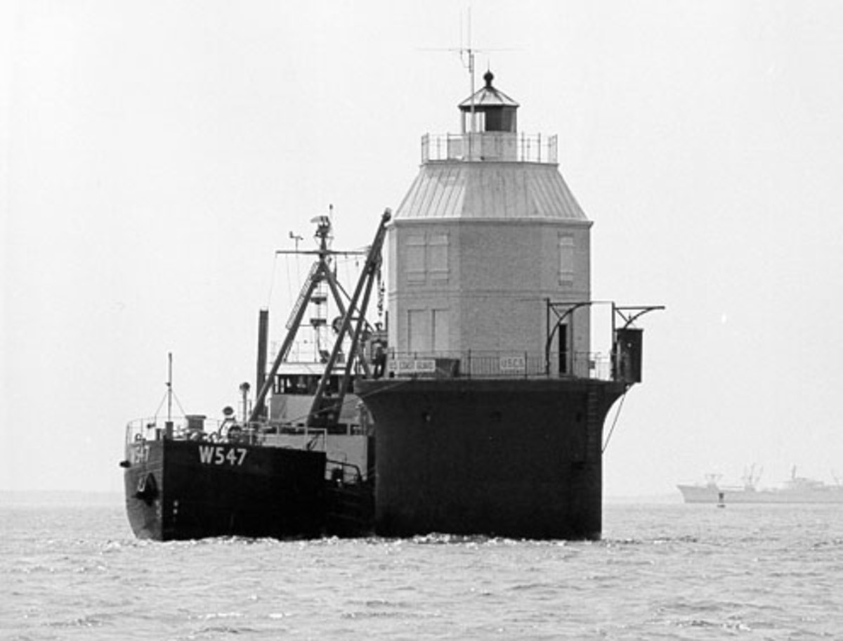 Baltimore Light being fitted with a radioisotope thermoelectric generator on May 20, 1964, making it the first and only nuclear-powered lighthouse in the United States. In the background is the NS Savannah, the first nuclear-powered merchant vessel.