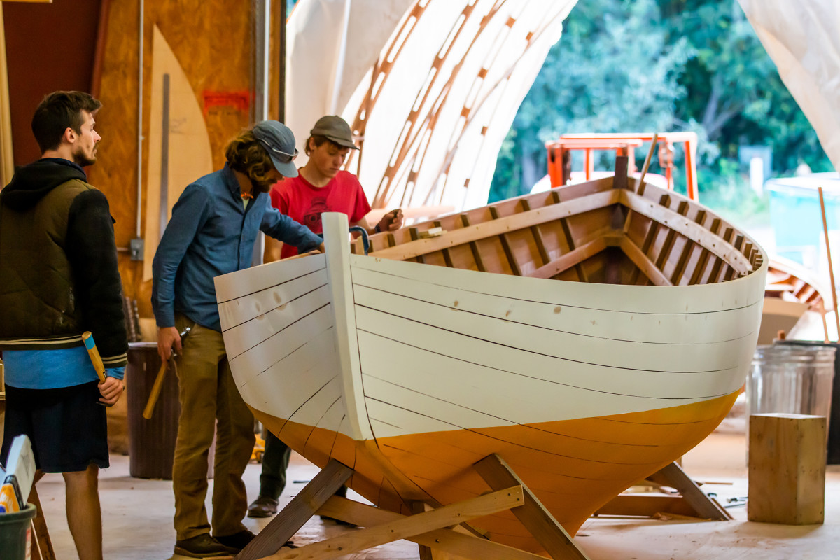 Two students inspect their work on a 28-foot Herreshoff Rozinante design.