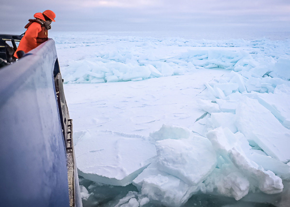 One of the science team members observes the thickest ice we encountered, which measured about 3 feet thick, despite the late season.