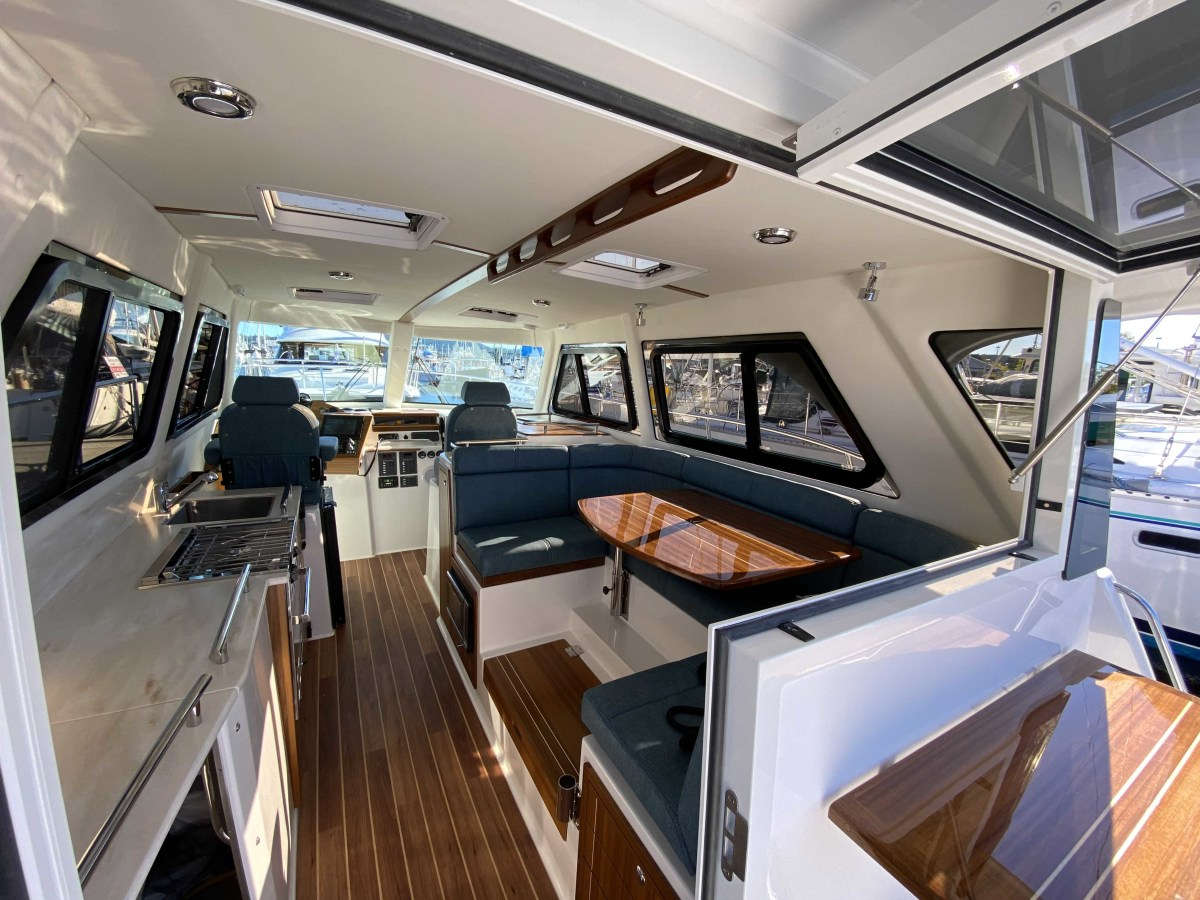Finished in fine teak, the C108's salon has 30 percent more livable space than previous Aspen models. Solar Guard windows provide good visibility underway from the C-shaped dinette and the twin Bentley helm seats.