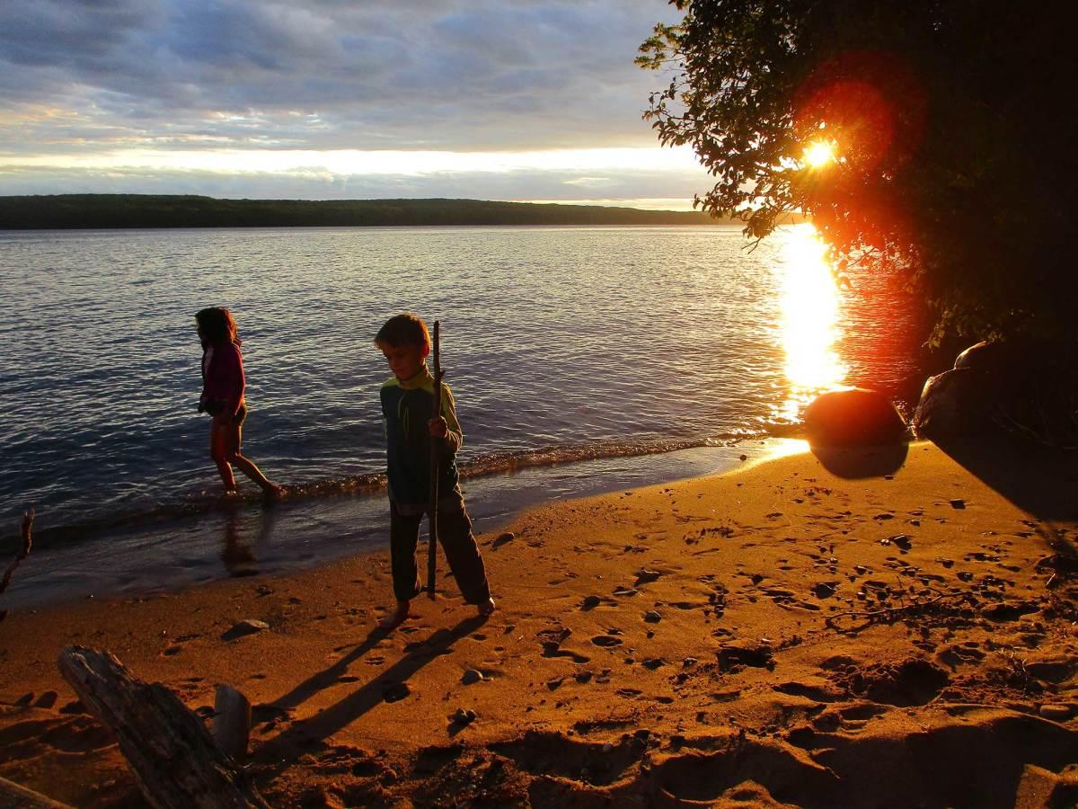The late-setting sun illuminates an Oak Island beach game of wilderness survival.