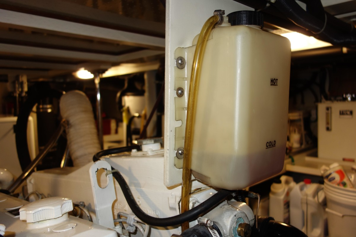 The black hose at the bottom of the overflow bottle carries expanded coolant from the engine's heat exchanger to the bottle. The tinted hose at the top directs overfilled or overheated coolant toward the bilge.