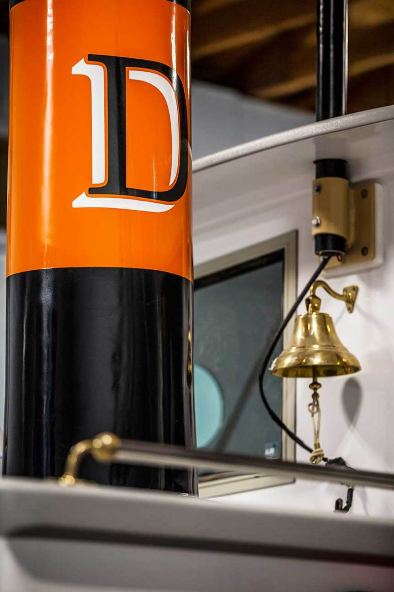 The dry stack painted with Devlin's orange, black and white livery. Traditional appointments include a brass bell and towing hardware on the aft flush deck.