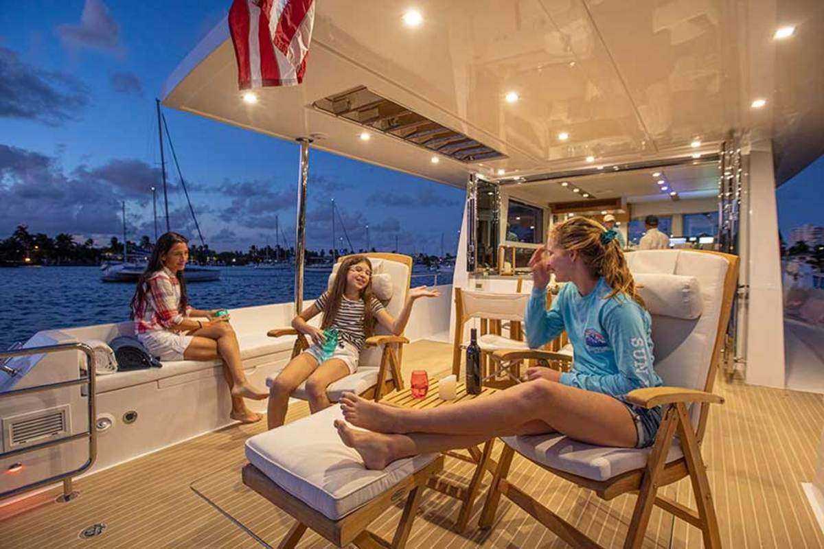 "The Outback 50 sports an ""infinity"" aft deck. Farther aft, removable stainless rails add protection to a step-down swim platform. The aft-deck setup invites lounging with movable teak furniture, though the space can be cleared for PWC, dive equipment or any number of water toys."