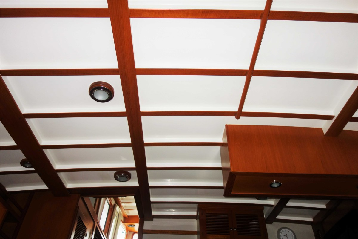 This fiberglass headliner has been nicely capped with teak and looks beautiful. There may be some access to the underside of the deck above if the lights are removed, but other than that, chasing a leak will be challenging.