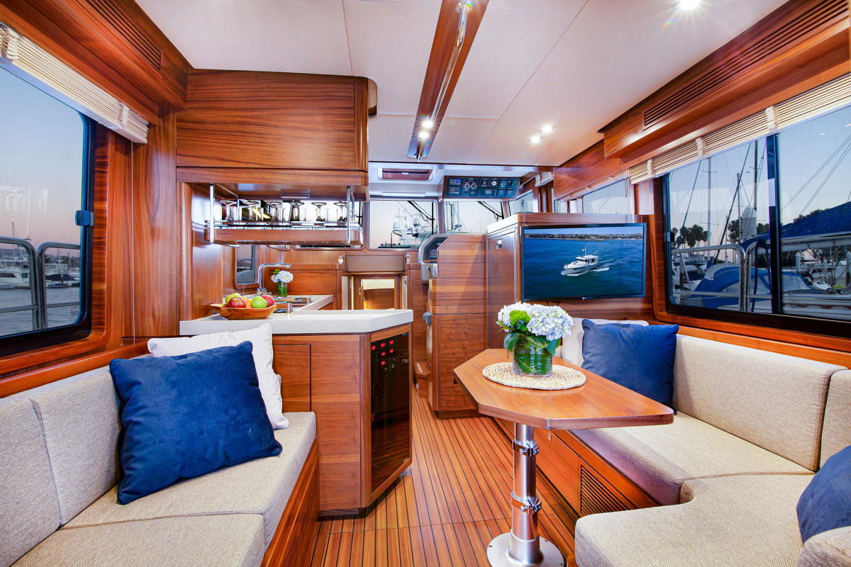 The salon is arranged for both cruising and living aboard, with large windows and overhead handrails for safety.