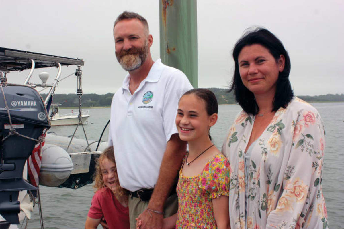 """The harbormaster of Wellfleet, Mass., Will Sullivan, is shown here at the town dock with his two children and wife, Bri. """"Family is important to me,"""" he says."""