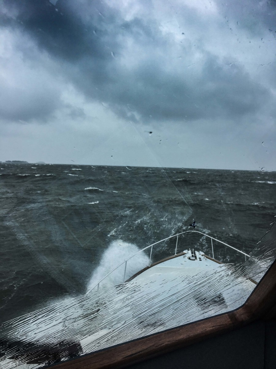 A gale arrived earlier than expected for the author, yet rigid preparation resulted in a safe passage.